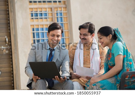Real estate agent showing online content on laptop to rural Indian family Royalty-Free Stock Photo #1850055937