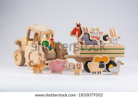 wooden kids tractor toy with trailer and cartoon agricultural animals isolated on white background, close view