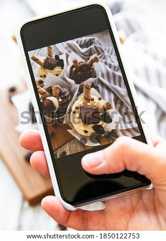 Girl makes a photo of cupcakes on a smartphone