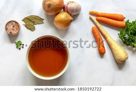 Flat lay of homemade beef bone broth in a bowl with ingredients. Contains minerals and healthy nutrients, including vitamins, amino acids, and essential fatty acids.  Royalty-Free Stock Photo #1850192722