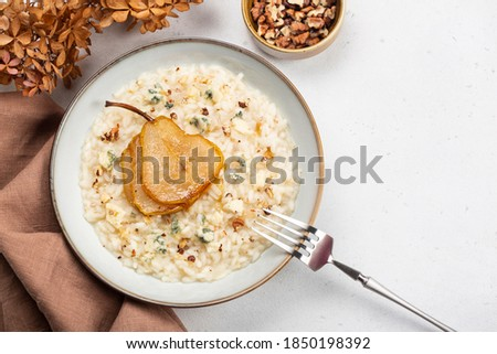 Risotto with gorgonzola cheese, pear and walnuts. Top view. Royalty-Free Stock Photo #1850198392