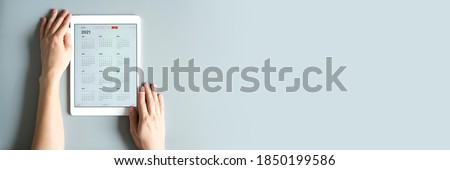 a tablet with an open calendar for 2021 year in a womans hands on a gray background. banner. space for text