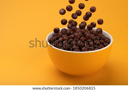 Chocolate Corn balls falling in bowl over yellow background with copy space, healthy breakfast cereal Royalty-Free Stock Photo #1850206825