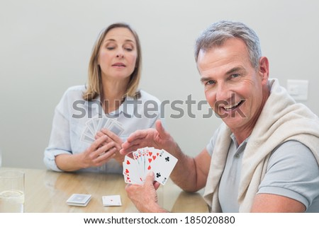 Portrait of a man playing cards with woman at home #185020880