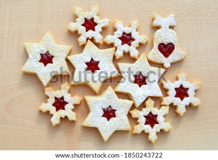 Homemade linzer cookies in a shape of snowflakes, stars and bell filled with strawberry jam, top view