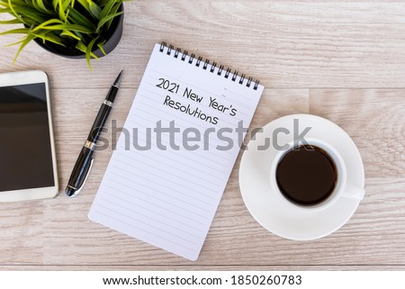 2021 New Year's Resolutions text on note pad with smart phone and cup of coffee #1850260783