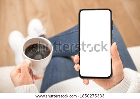 woman's hand holding white mobile phone with blank desktop screen and coffee cup. Top view mockup image of woman holding black mobile phone with blank white desktop screen with coffee cup
