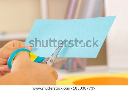 Kid hands cutting light blue colored paper with scissors. Education, learning, paper craft, entertainment Royalty-Free Stock Photo #1850307739