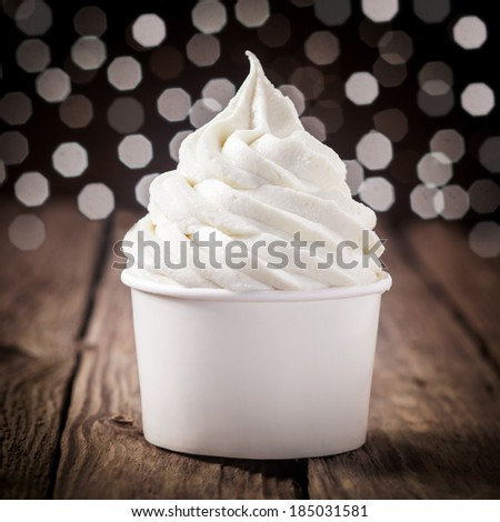Tub of creamy vanilla or tangy lemon ice cream on an old wooden bar counter with a bokeh of festive party lights Royalty-Free Stock Photo #185031581