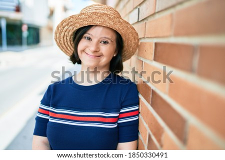 Beautiful brunette woman with down syndrome wearing a summer hat at the town on a sunny day leaning on a bricks wall Royalty-Free Stock Photo #1850330491