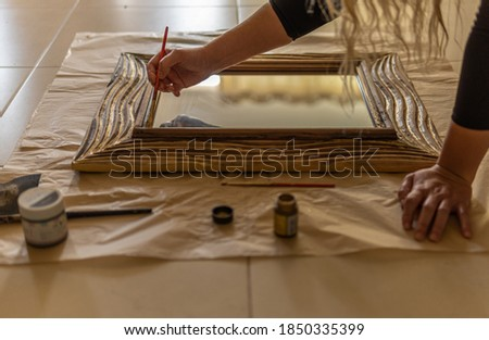 Painting and restoring the wooden frame of a mirror. Backlit image of a restoration workshop