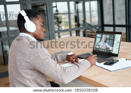 Serious african business man or black male student wearing headphones conference video calling, watching webinar online, social distance learning or working using laptop at home office, taking notes. Royalty-Free Stock Photo #1850338108