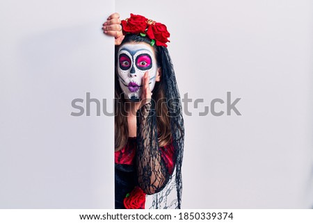 Young woman wearing day of the dead custome holding blank empty banner hand on mouth telling secret rumor, whispering malicious talk conversation