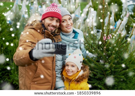 family, winter holidays and people concept - happy mother, father and little daughter buying christmas tree and taking selfie with smartphone at street market over snow
