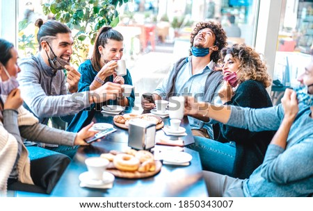 Friends having fun drinking and eating at coffeehouse - Young people talking together at restaurant cafeteria - New normal lifestyle concept with happy men and women at cafe bar - Bright azure filter Royalty-Free Stock Photo #1850343007