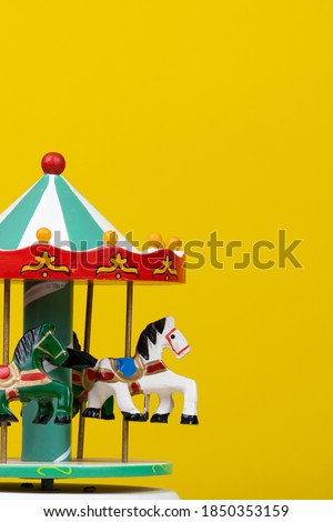 colorful carousel toy in yellow background. Vertical Royalty-Free Stock Photo #1850353159