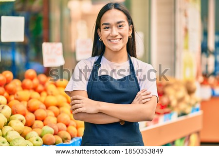 Young latin shopkeeper girl with arms crossed smiling happy at the fruit store. Royalty-Free Stock Photo #1850353849