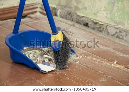Clean up after repairs. Sweep up construction debris with a brush in a dustpan. Sweeping at home. Tools for cleaning the house. Make home repairs. The dust and debris after the renovation. #1850405719