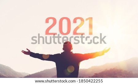 Man raise hand up on sunset sky at top of mountain and number 2021 abstract background. Happy new year and holiday celebration concept. Vintage tone filter effect color style. Royalty-Free Stock Photo #1850422255