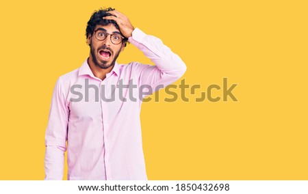 Handsome young man with curly hair and bear wearing business clothes surprised with hand on head for mistake, remember error. forgot, bad memory concept.  Royalty-Free Stock Photo #1850432698