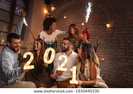 Group of young friends having fun at New Year's party, holding illuminative numbers 2021 representing the upcoming New Year and waving with sparklers at midnight countdown #1850440330