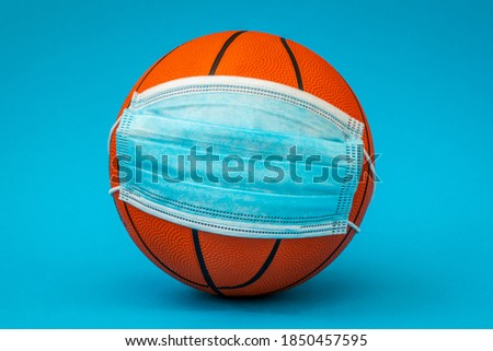Basketball ball with surgical medical face mask on the blue background. Concept for Coronavirus COVID 19 pandemic and epidemic affecting basketball seasons game suspend.