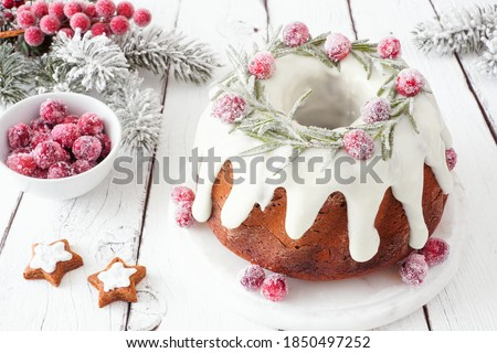 Christmas gingerbread cake with eggnog cream cheese frosting and wreath of snowy rosemary and cranberries. Table scene with a white wood background. Royalty-Free Stock Photo #1850497252