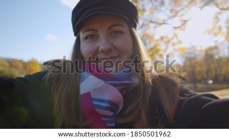 Beautiful young woman in fashionable fall clothes taking selfie at park. Pretty millennial lady making photo of herself at walk outdoors. Woman having video call outside