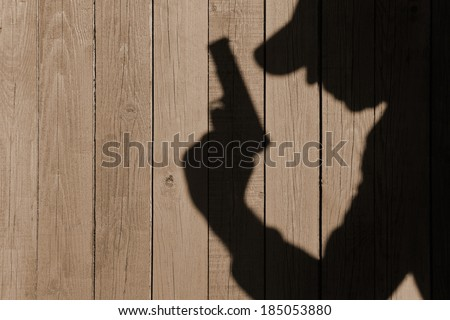 Gangster or investigator or spy silhouette on natural wooden wall. You can see more silhouettes and shadows on my page. #185053880
