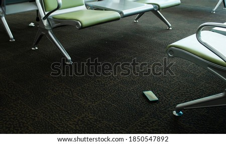 Smartphone found on carpet under the seat of a international airport, Mobile phone dropped on the ground and forgotten, Concept of mobile communication in travel and lost gadgets in the airport,  #1850547892