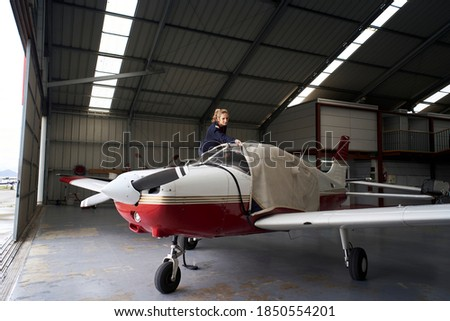 Young female pilot covering light aircraft with protective cover in hangar. Royalty-Free Stock Photo #1850554201
