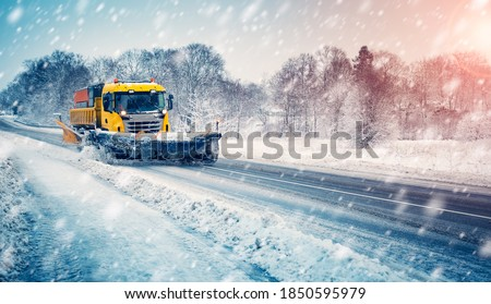 Snow plow truck cleaning snowy road in snowstorm. Snowfall on the driveway. Royalty-Free Stock Photo #1850595979