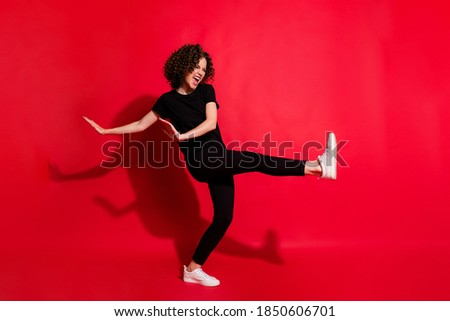 Photo portrait full body view of girl kicking raising leg dancing isolated on vivid red colored background Royalty-Free Stock Photo #1850606701