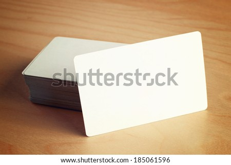 Stack of blank horizontal business cards with round corners propped up another with copy space for your design