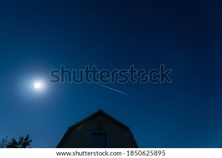 Cloudless, blue, summer night. Starlink's sputnic fly over the house against the moon. Deep night, starry sky.