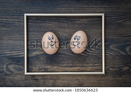 Picture golden frame and two funny eggs smiling on dark wooden wall background, close up. Eggs family emotion face portrait. Couple eggs with happy face for love concept