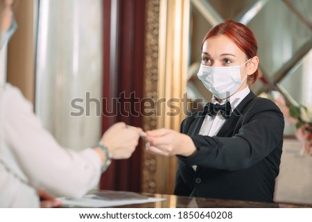 Check in hotel. receptionist at counter in hotel wearing medical masks as precaution against virus. Young woman on a business trip doing check-in at the hotel Royalty-Free Stock Photo #1850640208