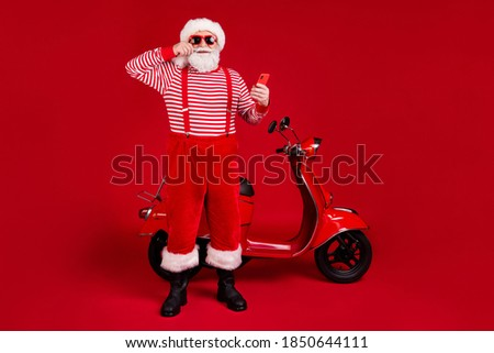 Full length body size view of his he handsome cheerful cheery glad bearded Santa father riding moped using device blogging sale discount isolated bright vivid shine vibrant red color background