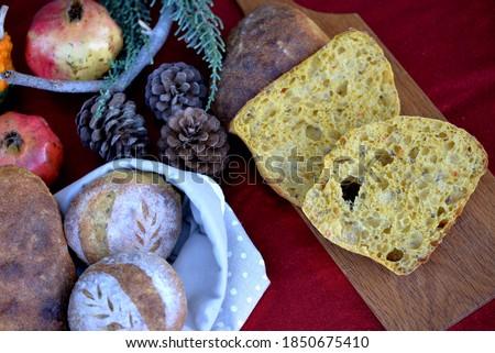 Christmas bread with pumpkin mash; bread bag with small breads - bread buns and ciabatta; bread texture of ciabatta cut in half on wooden board #1850675410