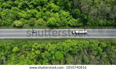 Aerial. Gasoline fuel truck driving by the highway road between green forest. Top view. Royalty-Free Stock Photo #1850740816