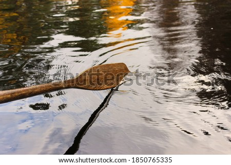 A wet, wooden oar shot in the middle of rowing a boat, submerged into the rippling surface of a lake with the reflection of a Swedish autumn forest in Sweden on it. Royalty-Free Stock Photo #1850765335