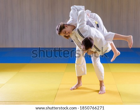 Adult male judoka throwing young female judo girl with hip throw Royalty-Free Stock Photo #1850766271