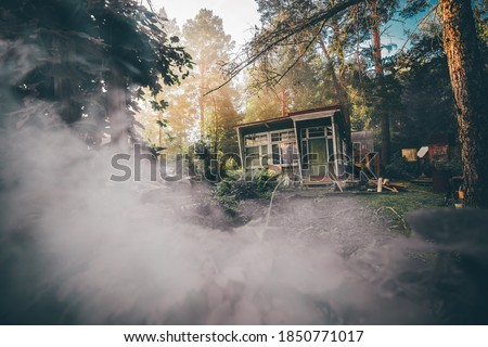 A wide-angle view of an old desolate one-story summer shack with glass veranda surrounded by conifer trees and bushes of the garden and lit by the warm evening sun, with a smoke in the foreground Royalty-Free Stock Photo #1850771017
