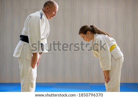 Young female judo girl showing respect to old judo teacher Royalty-Free Stock Photo #1850796370