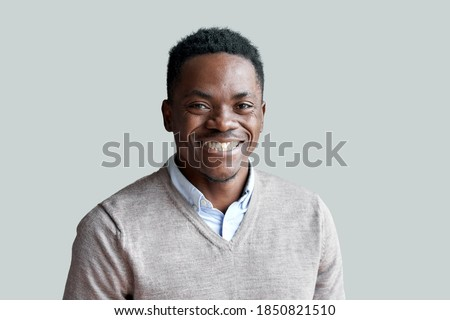 Smiling cheerful young adult african american ethnicity man looking at camera standing at home office background. Happy confident black guy posing for headshot face front close up portrait. Royalty-Free Stock Photo #1850821510