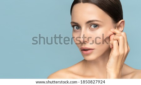 Woman without makeup touching cheeks after glycolic acid peel, has signs of aging skin on her face, looking at camera, isolated on studio blue background. Beauty skincare, cosmetology facial treatment