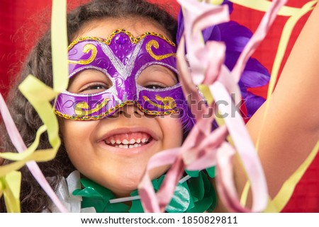 Small girl with mask and necklaces used in Brazil's carnival playing with streamers, red background, selective focus.