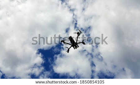 Controlled drone with mounted camera flies in cloudy blue sky.