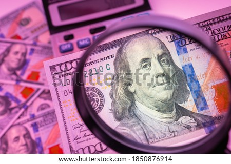 Watermarks on a dollar. Fake money. Concept - counterfeiters. Magnifying glass over the bills. Watermarks are visible under ultraviolet light. Concept - checking authenticity. Franklin. Calculator