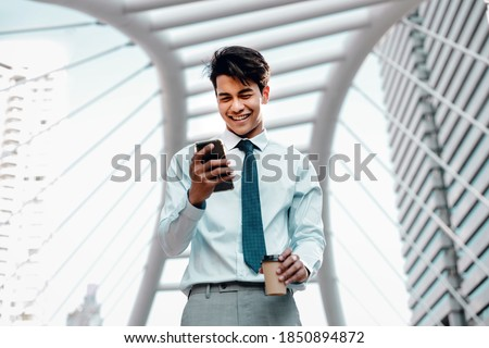 Portrait of a Smiling Young Asian Businessman Using Mobile Phone in the City  Royalty-Free Stock Photo #1850894872